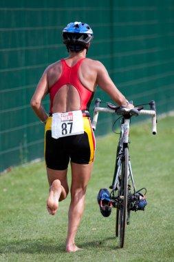 Triathlete pushing his bike