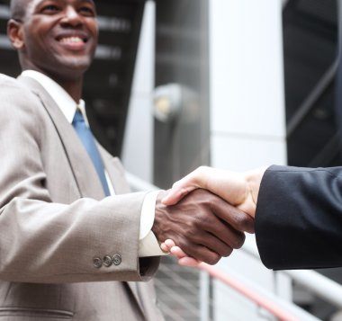 African American businessman shaking hands with caucasian busine