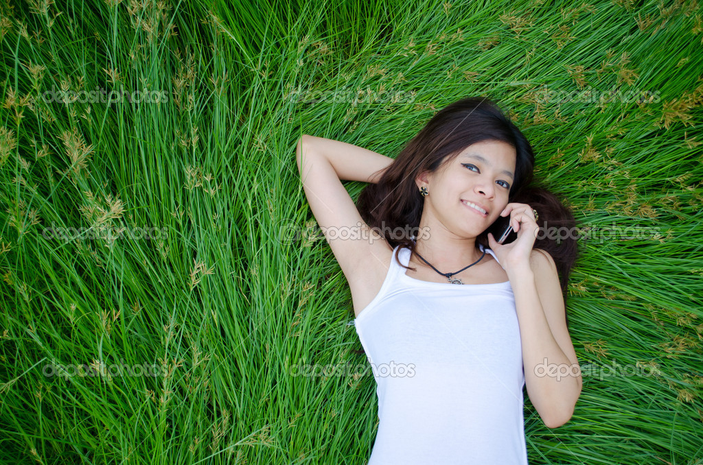 Asian girl on phone lying on a meadow