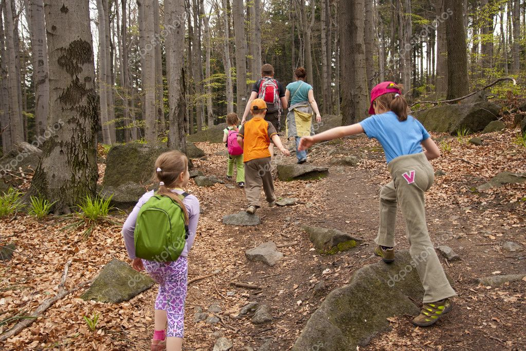 Children with their parents are going for a walk in the woods