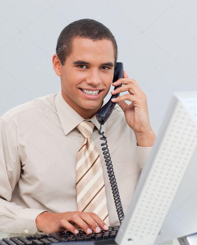 Joven empresario hablando por tel fono en la oficina for Telefono de la oficina