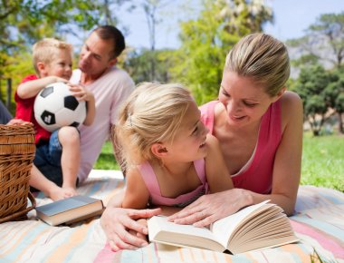 Mother and her daughter reading at a picnic with their family