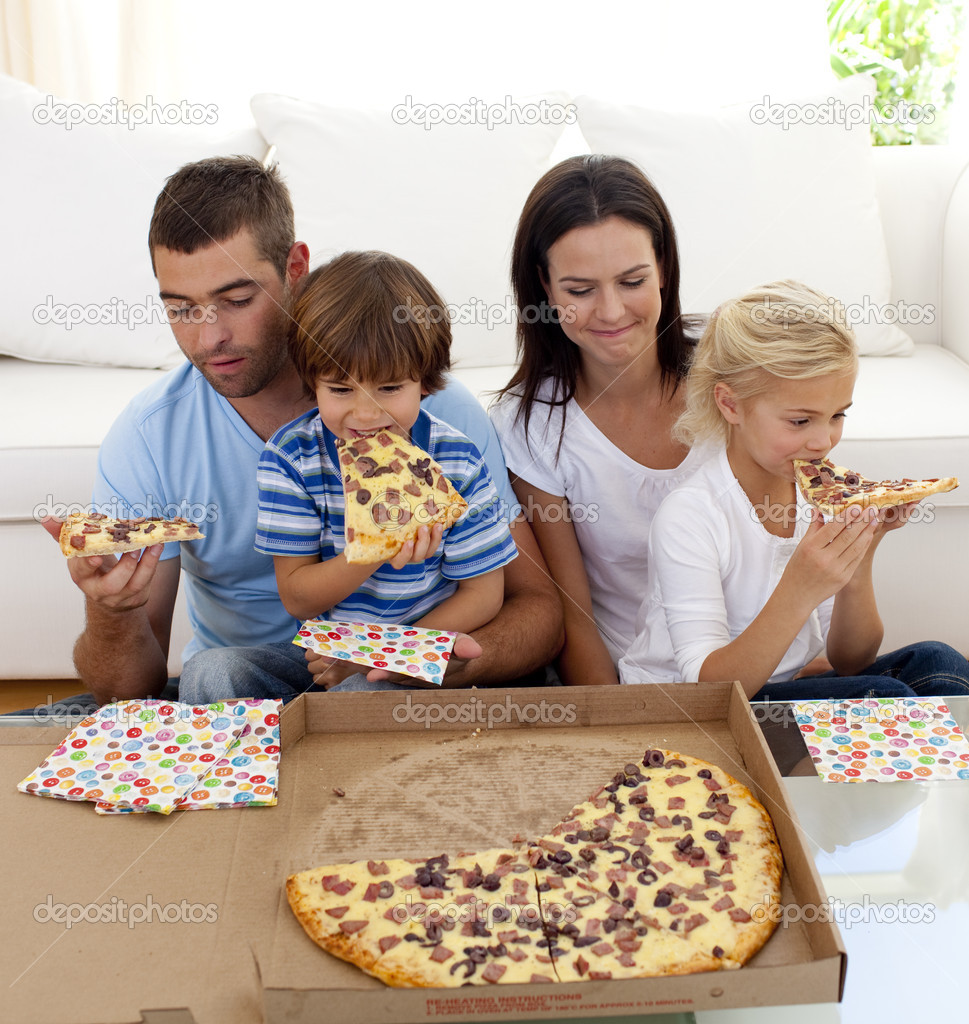 family eating pizza in living room stock photo wavebreakmedia 10299718. Black Bedroom Furniture Sets. Home Design Ideas