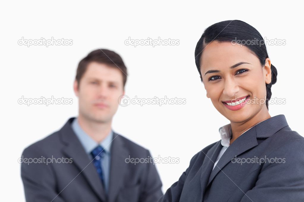 close up of smiling saleswoman with co worker behind her stock