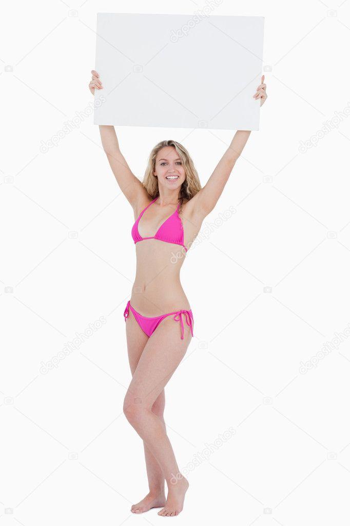 3197af0b02 Giovane donna alzando un poster bianco sopra la sua testa contro uno sfondo  bianco — Foto di Wavebreakmedia