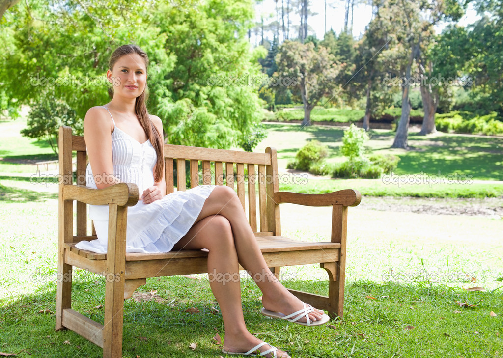 Woman With Her Legs Crossed Sitting On A Park Bench Stock Photo Wavebreakmedia 10330951