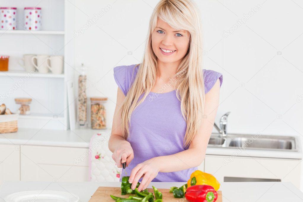 Beautiful blonde woman cutting vegetables in modern kitchen inte ...