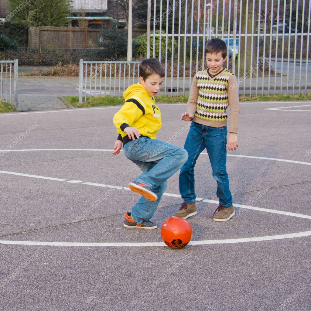 two boys kicking football on the sports playground  u2014 stock photo  u00a9 tetyanka  10222923