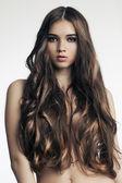 Krásná žena s dokonalou kůži a dlouhé kudrnaté vlasy