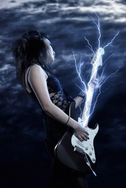 Woman rock star with guitar in hands and lightning storm