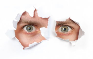 Eyes looking through a hole in a paper isolated stock vector