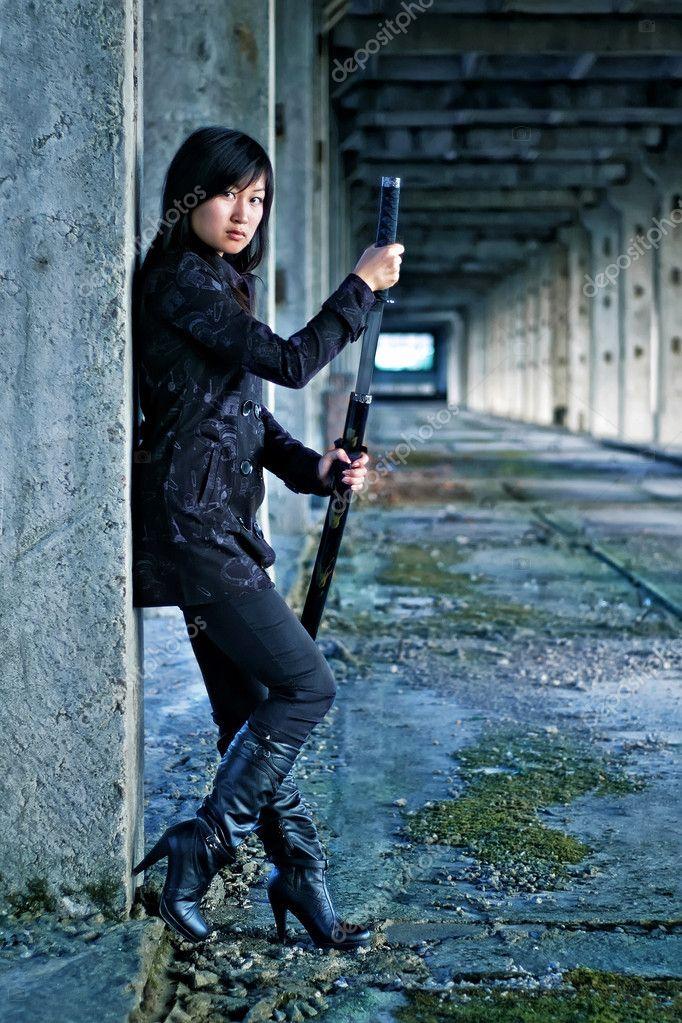 Asian girl with katana in ruins