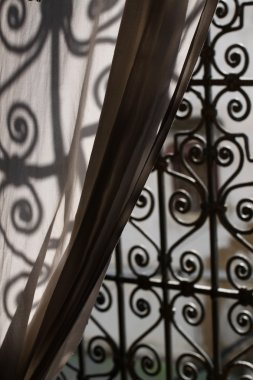 An elegant iron window in a Moroccan Market draped by a Curtain