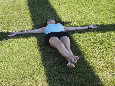 Young woman laying over cross shadow in the grass