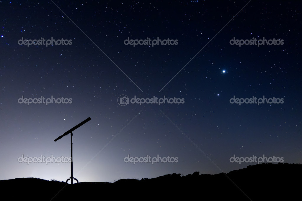 Night shot with a silhouette of a telescope