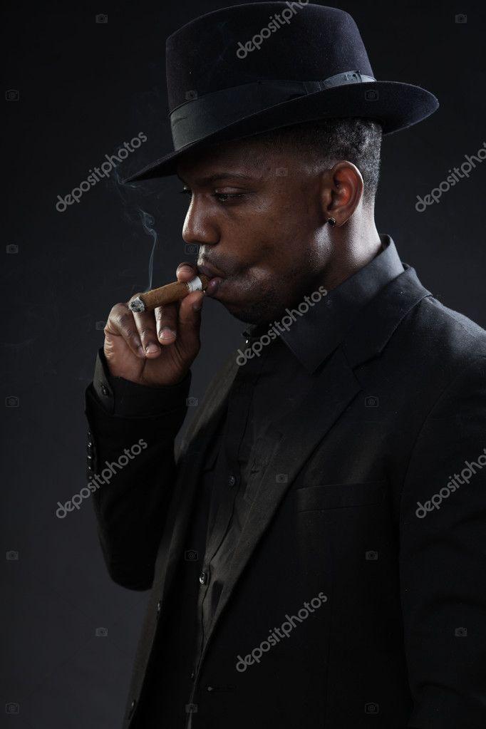 Joven negro lleva traje y sombrero gangster estilo fumar cigarro aislado  sobre fondo oscuro. Retrato de estudio — Foto de ... 283f5276092