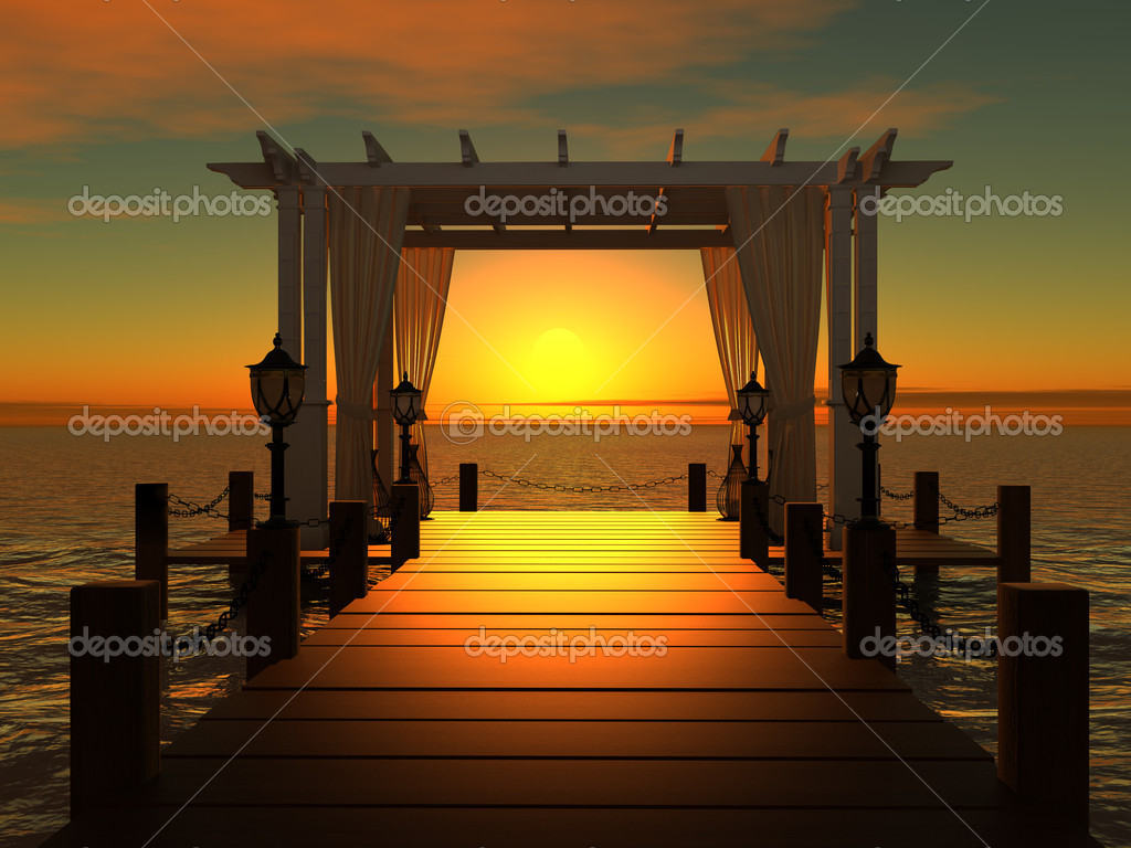 Wedding gazebo on the wooden pier into the sea with the sun at sunset