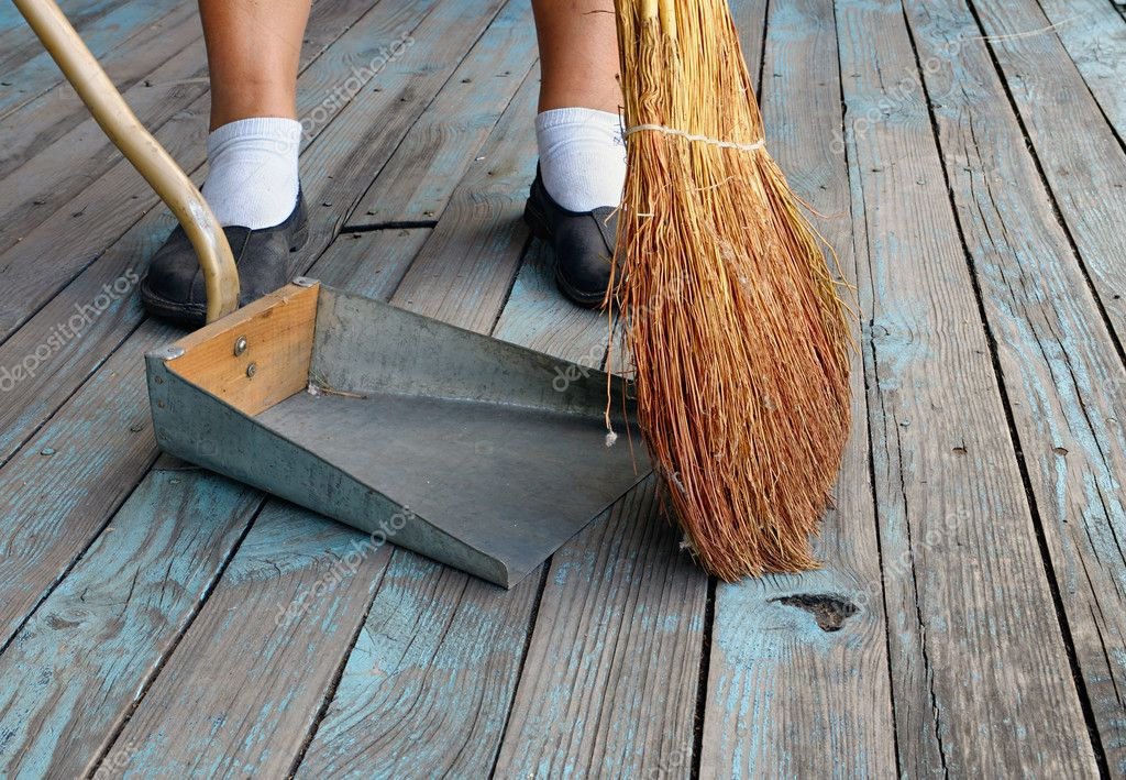 an person with a broom sweeping floor of the boards into dustpan u2014 photo by horten