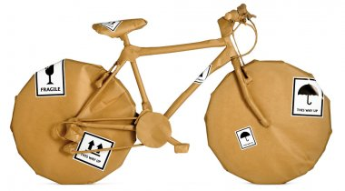 Bicycle wrapped in brown paper ready for an office move isolate