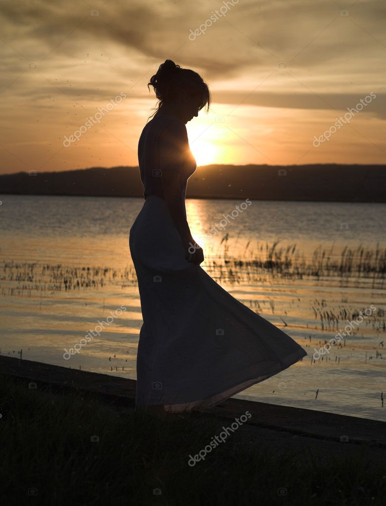 Young, slim lady dances alone at the beach, sunset