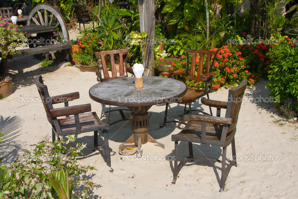 Table and chairs in a tropical garden