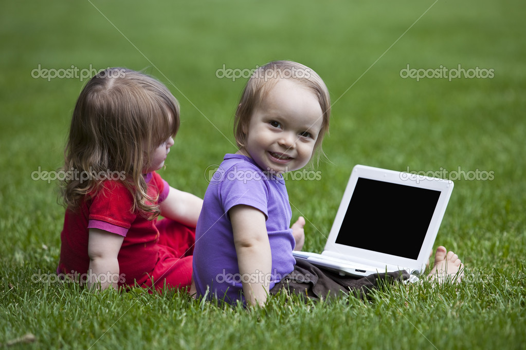 Babies with Notebook sitting on meadow
