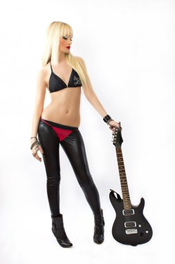 Sexy blonde girl in red thong posing with black electric guitar