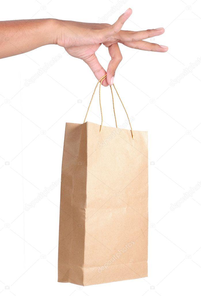 Hand holding white paper bag