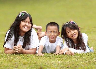 Portrait of happy kids lying on the grass
