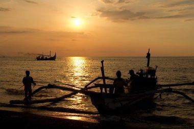 Fishermen at beach during sunset