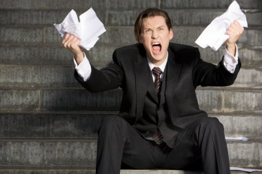 Photo of screaming businessman with two sheets of paper in his hands