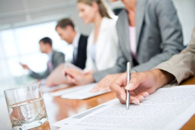 Woman's hand with pen over document on background of business group