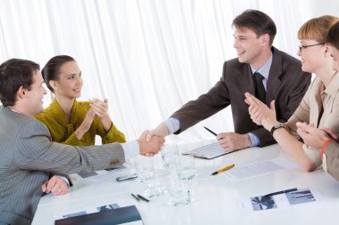 Business partners shaking hands after striking deal while their co-workers applauding stock vector