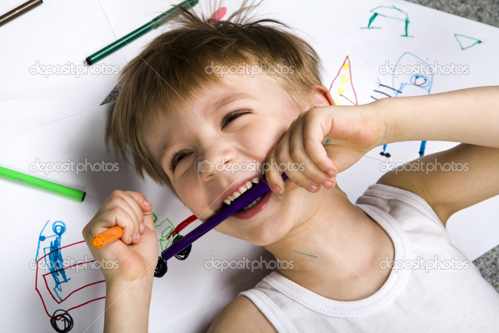 Laughing boy lying on his drawing with felt-tip pen in his teeth