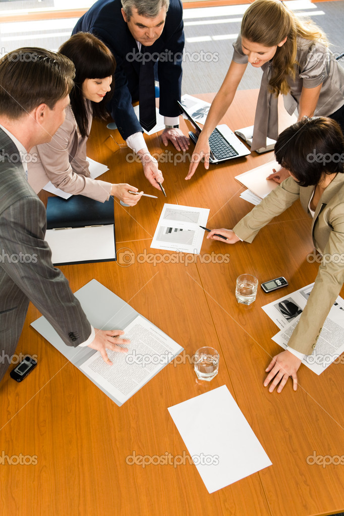 Team of confident pointing to a business project at seminar
