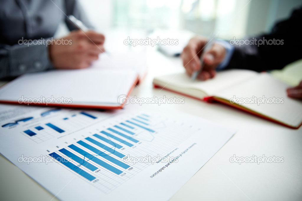 Image of document with charts on background of male and female hands with pens over open notebooks at seminar stock vector