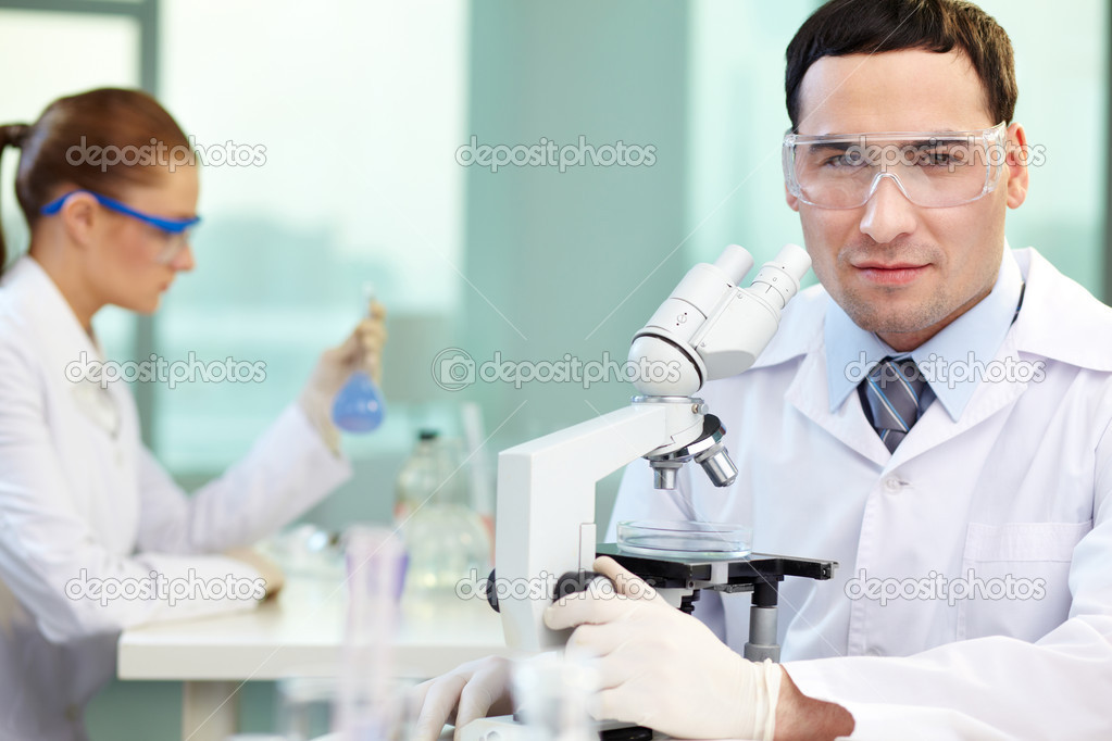 Portrait of young clinician looking at camera in working environment