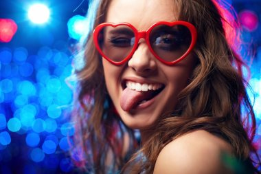 Portrait of a girl wearing heart-shaped glasses playfully showing her tongue stock vector