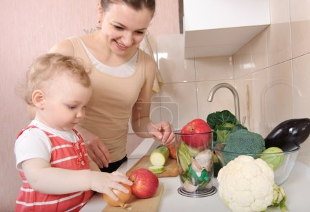 Photo for Young mother preparing fresh vegetable salad with her baby daughter - Royalty Free Image