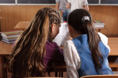 Photo for Two schoolgirls chating in classromm during lesson - Royalty Free Image