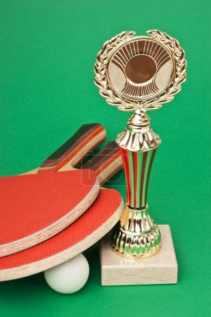 Sports awards and tennis racquets on green table