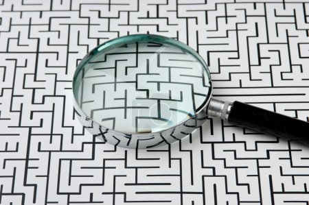 Magnifying glass on the background of the labyrint...