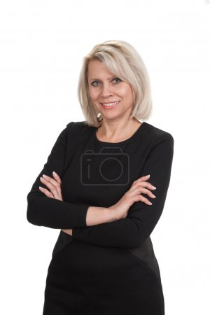Mature businesswoman standing with arms crossed against