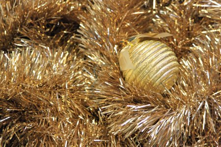 Photo for Golden christmas ball on a golden tinsel - Royalty Free Image