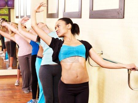 Women group in aerobics class do exercises ....