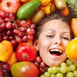 Young woman in group of fruit. Healthcare....