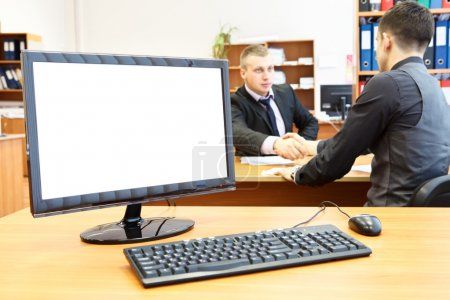 Office computer on desk and two businesspersons on background handshaking