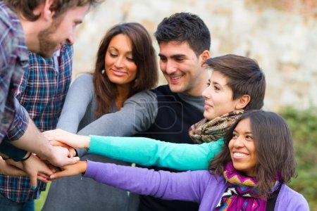 Photo pour Étudiants multiraciaux avec des mains sur la pile - image libre de droit