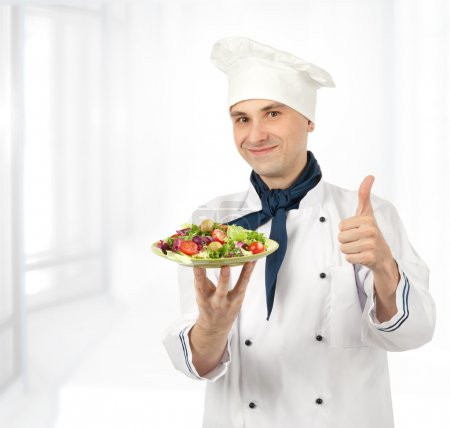 Cook man holding a plate with healthy vegetables salad