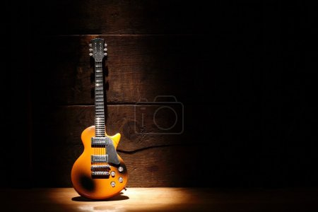 Photo for Music concept.Electric guitar standing near wooden wall under beam of light - Royalty Free Image